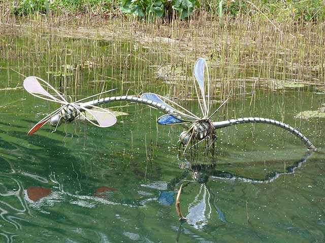 Large metal dragonfly sculptures in a pond